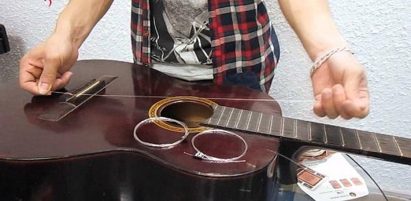 Dùng kìm tháo dây đàn Guitar theo chiều ngược kim đồng hồ Bước 3: Thay dây đàn Guitar mới Có 2 kiểu thay dây đàn Guitar Kiểu 1: Thay từng dây: Kiểu này chúng ta thường thực hiện khi chỉ bị đứt một vài dây trong khi các dây khác đều còn mới có thể tiết kiệm chi phí mua dây đàn. Kiểu 2: Thay toàn bộ: Kiểu này thường làm khi bộ dây đã được sử dụng lâu (tùy vào loại dây), và âm thanh của dây bắt đầu xuống, màu dây sẫm đi hoặc rỉ sét. Sau khi xác định những dây đàn được thay bạn lấy dây ra lần lượt thực hiện: – Gắn đầu dây vào các chốt đàn: đưa dây xuống lỗ sau đó ghim chốt xuống để cố định. – Xỏ dây qua các lỗ trên khóa đàn chú ý tới dây nào thì xỏ chốt vào luôn và khóa chúng lại, và không xỏ nhầm số thứ tự của các dây. – Vặn khóa đàn theo chiều ngược kim đồng hồ, vừa vặn các bạn vừa để tay lên ấn nhẹ vào chốt đàn để tránh việc chốt đàn bị đẩy ra. – Vừa vặn chốt các bạn vừa dùng ngón tay gảy nhẹ dây đàn khi nào dây đàn căng vừa phải bắt đầu phát ra âm thanh thì dừng lại. Cứ thế bạn thực hiện tương tự với các dây còn lại là xong.